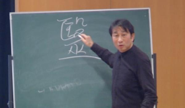 黒板に毉を書く院長写真